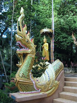 estátua de phaya naga cor verde e dourada em um templo budista