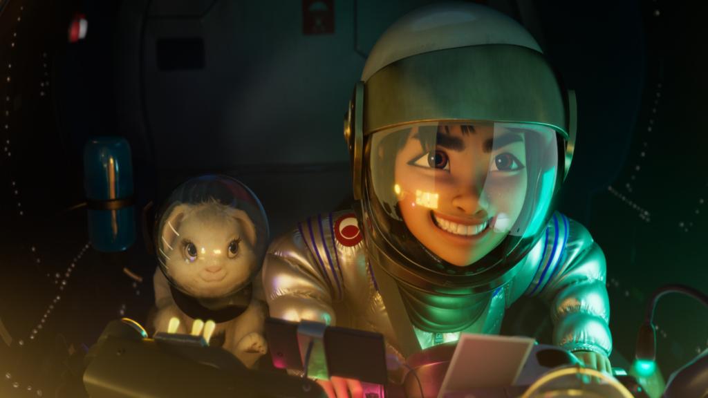 Fēi Fēi em trajes de astronauta: roupa cinza-metálica, capacete, sorrindo, aparece tanto os dentes superiores quanto inferiores. Seus olhos são castanho-claro e estão bem abertos. Ela está com uma expressão de muita felicidade. Ao lado dela tem um coelho branco, que também está de capacete.