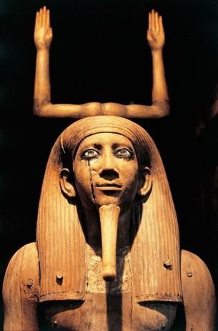 Representação isolada do ká, com as mãos pra cima como se estivesse louvando ou agradecendo. Na parte de baixo tem um busto, representando um egípcio, toda tonalidade é marrom.