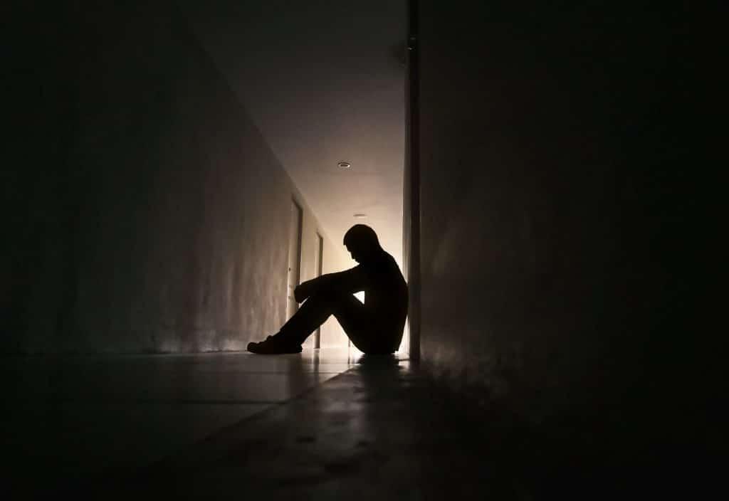 Homem sentado num corredor escuro, com uma leve fonte de luz ao fundo.