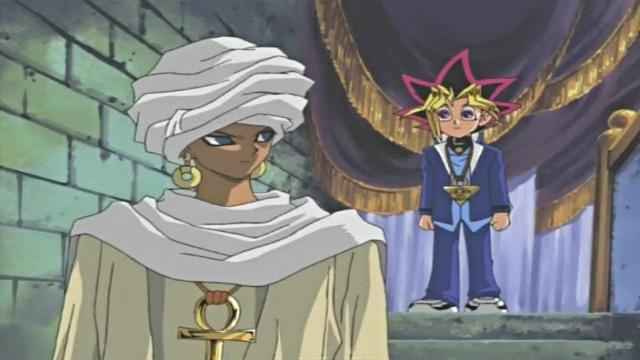 Representação de Shadi, do mesmo jeito que a imagem anterior; a diferença é que agora ele está dividindo a cena com Yūgi Mutō, que está atrás dele, com calça e paletó azul escuro, cabelo dourado. O cenário tem umas cortinas roxo-escuras com detalhes em amarelo-ouro.