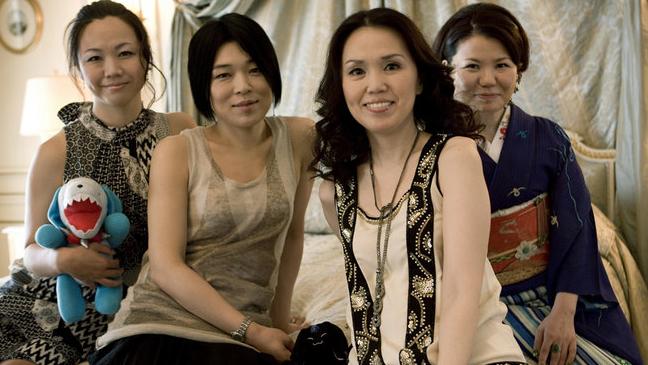 """Quatro mulheres sentada no """"pé"""" da cama. Da esquerda para a direita, a primeira está de vestido e segurando um bichinho de pelúcia. A segunda está com uma roupa casual. Do lado está uma outra mulher com roupa casual e está usando um colar. A última mulher está vestindo um quimono. Todas estão olhando para a sua direção e estão felizes com sorriso e gestos simpáticos."""
